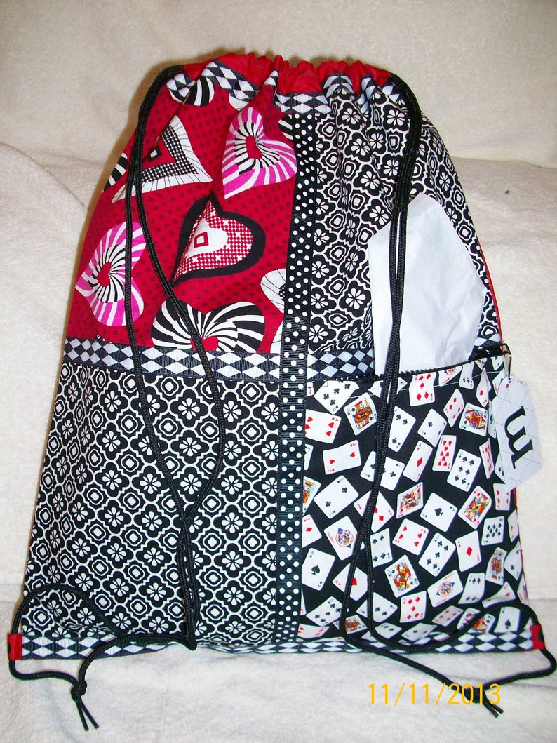 cards and hearts in red and black on a red ripstop nylon drawstring backpack with front zipper pocket