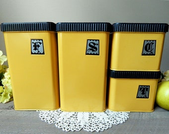Vintage Set of Four Lincoln Beautyware Tin Canisters in Yellow Harvest Gold with Black Hammered Wrought Iron Design Style Lids 1970s