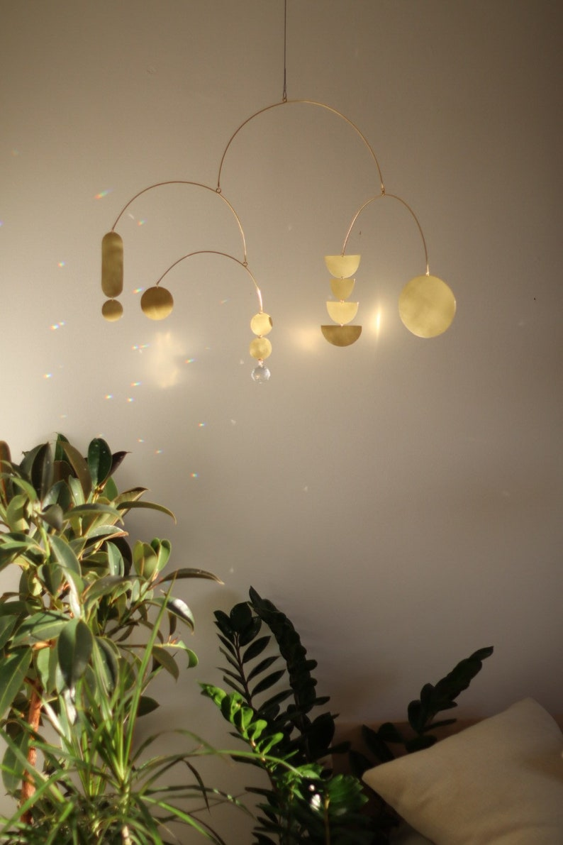 Starling kinetic brass mobile with glass crystal for modern nursery