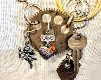 """Steampunk necklace full of love. Upcycled repurposed necklace, with chains, clock gears, hearts, beads, a Cupid and key to your heart 30"""" L"""