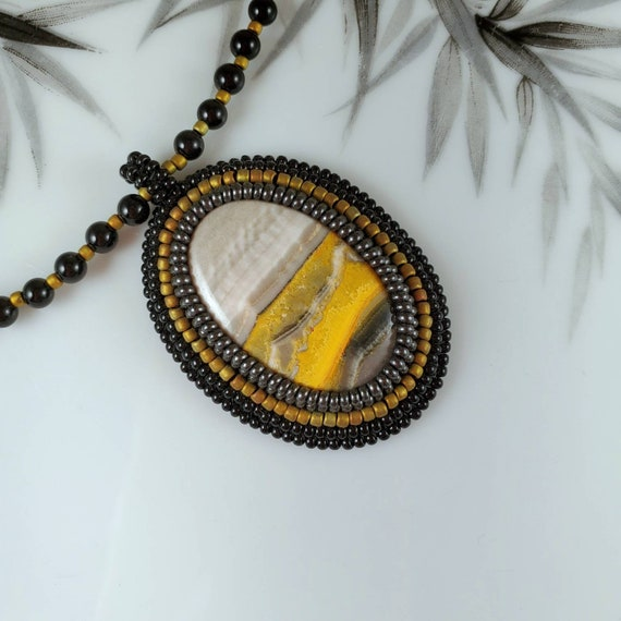 Natural art Bumblebee yellow jasper pendant in a hand beaded frame on black onyx and hematite  necklace. Foxxy Jewelry CynthiaFoxDesign