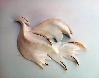 Bird of peace .Haven bird .Wall art. Wall hanging. White ceramic bird with gold decoration .Hanging on the wall sculpture.