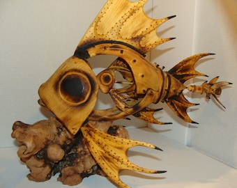 Mother of all fish. Hand carved Mechanical fish with propeller that turns by hand. Carving has saw blade teeth.