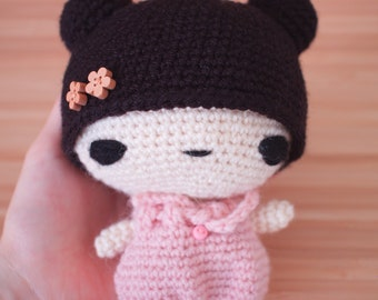 Chibi amigurumi doll with pastel pink dress and wooden flower button details