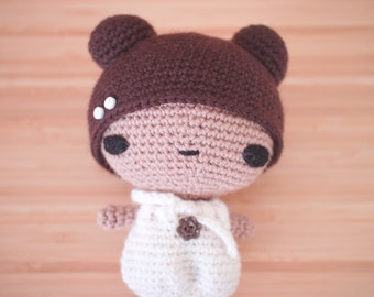 Crochet amigurumi doll with white dress and button details