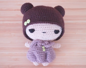 Crochet amigurumi doll with mauve purple dress and button details