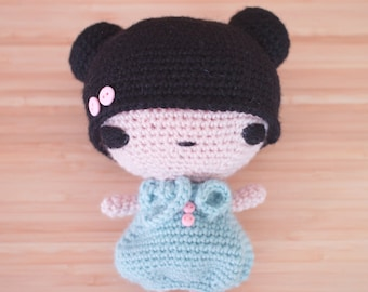 Chibi amigurumi doll with pastel mint dress and pink button details