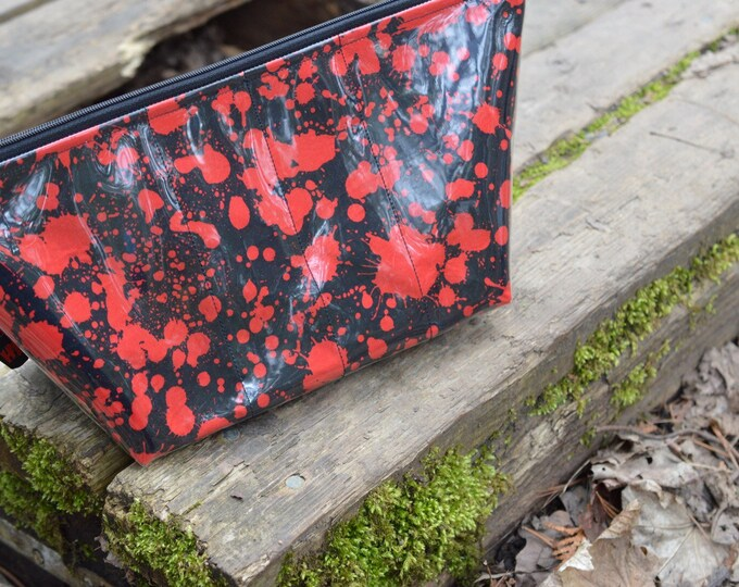 Zippered makeup bag in a blood splatter fabric with clear vinyl top layer