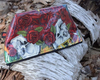 Zippered makeup bag in a skull and roses fabric with clear vinyl top layer