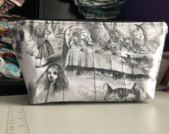 Zippered makeup bag in an Alice in Wonderland fabric with clear vinyl top layer