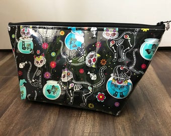 Zippered makeup bag in a sugar skull cat fabric with clear vinyl top layer