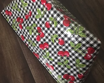 Zippered makeup bag in a gingham cherry fabric with clear vinyl top layer
