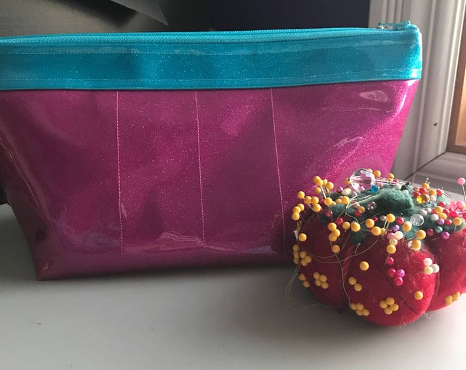 Zippered large makeup bag made of magenta and turquoise sparkle vinyl