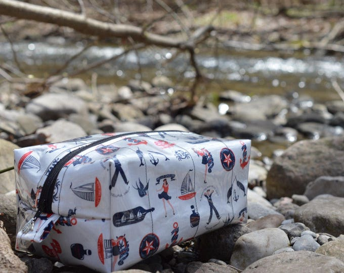 Zippered toiletry bag in a nautical fabric with clear vinyl top layer