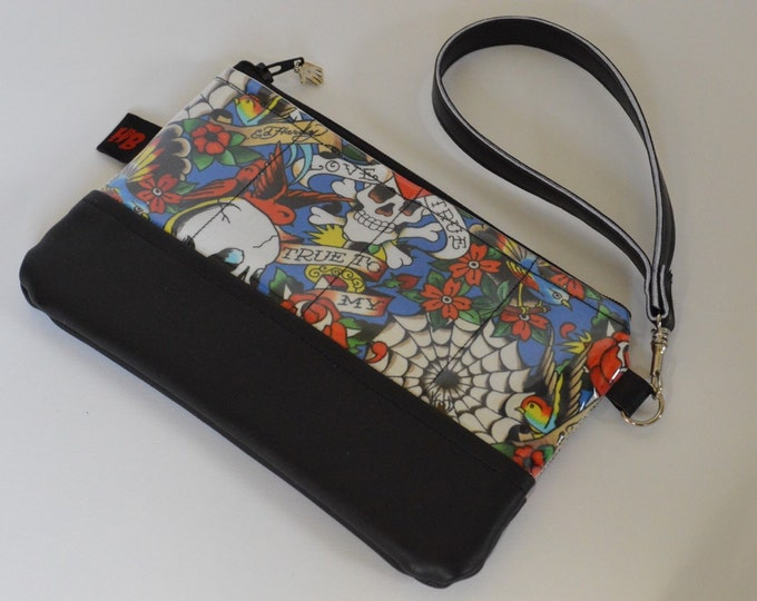 Zippered wristlet with strap in a retro tattoo flash fabric with black vinyl