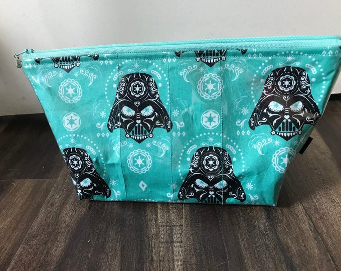 Zippered makeup bag in a sugar skull Darth Vader fabric with clear vinyl top layer