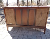Mid Century Modern Record Player Cabinet with AM FM Radio with built in speakers that are covered in a cane wood finish but does Not Work