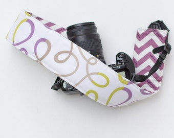 DSLR camera strap cover with lens cap pocket.  Loops with purple chevron.