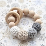 Rattle for baby. Teether. Neutral shades of grey, beige, white teething ring toy with crochet wooden beads.