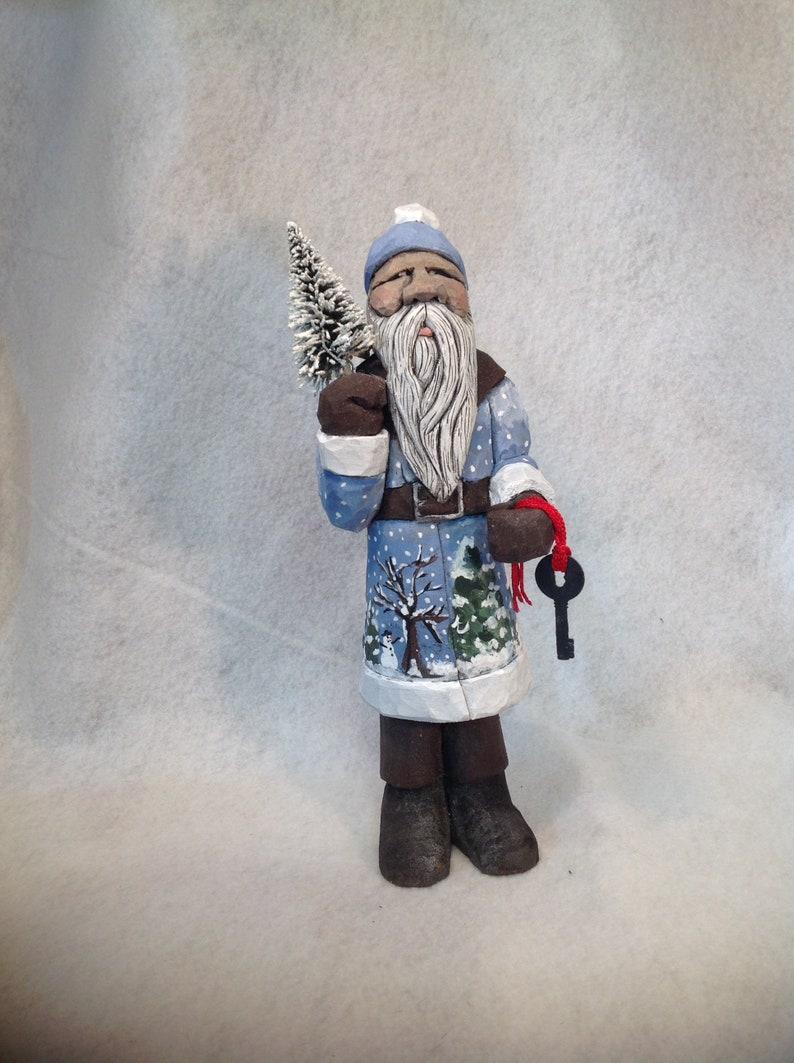 Carved santa in blue with winter scene