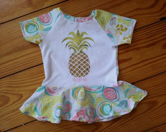 e69e61764ca5 Girl's Pineapple top with peplum and raglan short sleeves in a cotton tropical  print knit.