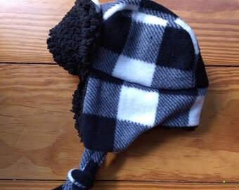 205597bbb20589 Buffalo plaid toddler trapper in black and white, hat fits up to 18 inches  around. Made of fleece and polyester fur lining with fleece ties.