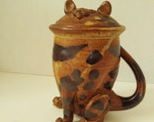Ceramic lidded Cat Mug. The lid of the mug is his face with perky ears. His tail is the handle. He is brown with dark irregular spots.
