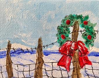 Christmas wreath on a cedar fence post, snowy mountains.