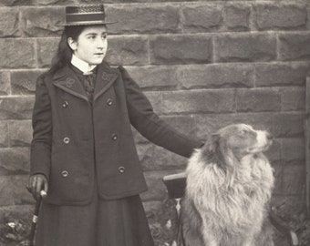 Vintage Photograph of a Young Lady Wearing a Wonderful Hat Holding a Cane with Her Hand on a Dog Sitting on a Chair Beside Her