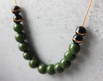 Long oliv green porcelain necklace with dark blue pearls with real gold lines