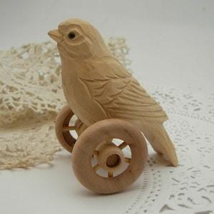 hand carved bird on wheels
