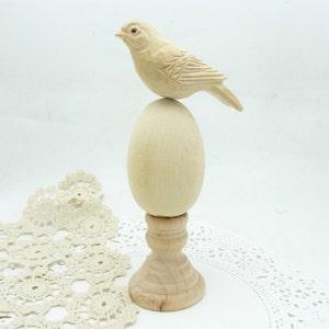 Hand carved wooden bird on egg pedestal.