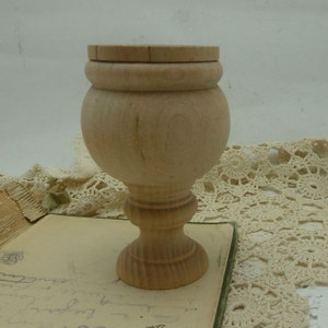 small  ready to decorate wooden urn  holds about 1/3 dry )cup It is 4 inches tall by 2 /12 inches wide  the bowl is 2 /14 tall by 2 /12 wide