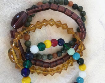 4 Beaded Bracelets.  Stretchy Beaded Bracelets in Jade and Amber, Clear Yellow, Lavender Cylinders and Multi Color Round Glass Beads.