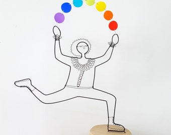 Wire sculpture, juggler with rainbow balls on wooden block, free standing sculpture. Handmade by Becky Crawford from Spacefruit