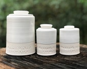 One urn. lidded customized urn for partial volume adult cremains. Multiple sizes shown for split ashes. shown in white