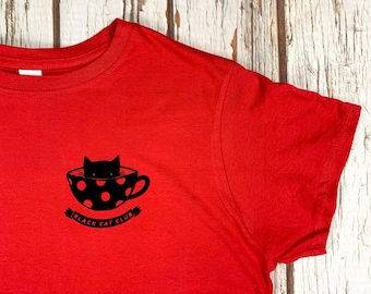 Black Cat Club Woman's red top with teacup and paw prints. Ladies T-Shirt.