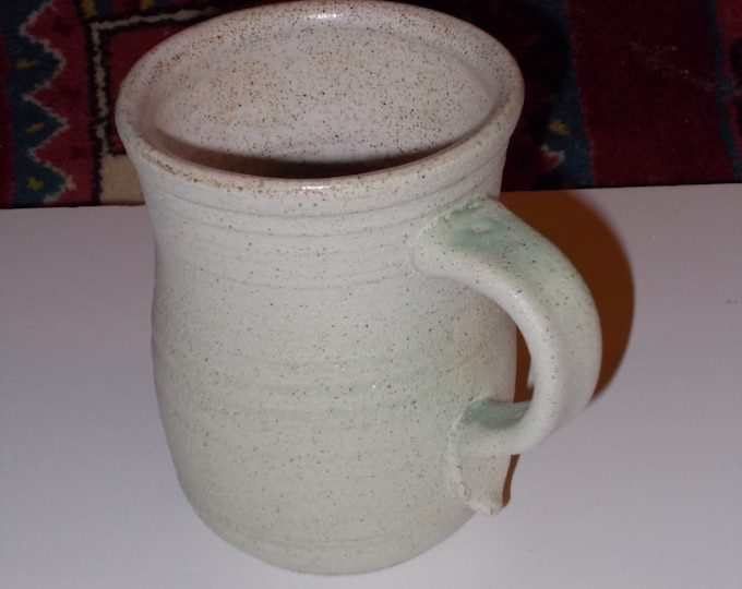 Small coffee mug with light green matt glaze