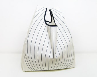 Reusable Shopping Bag, folded into a triangle, blue and white cotton, edged in black ribbon.