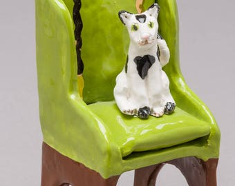 Ceramic / clay hand built sculpture of a white and black cat sitting in a formal chair.