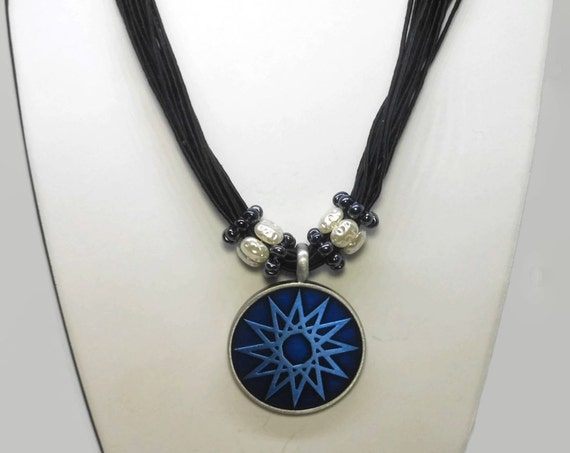 Blue star pendant, round blue epoxy pewter pendant, faux translucent seed pearl ringlets, multi-strand black cord, star or sun