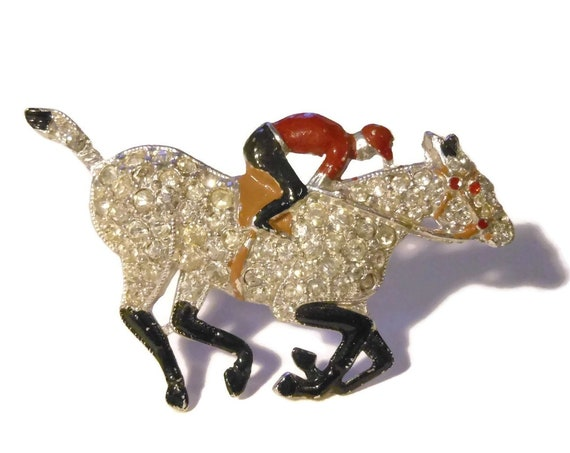 Jockey and horse brooch, pave rhinestone horse with enamel rider and hoofs, clear rhinestones, red and black enamel, 1950s