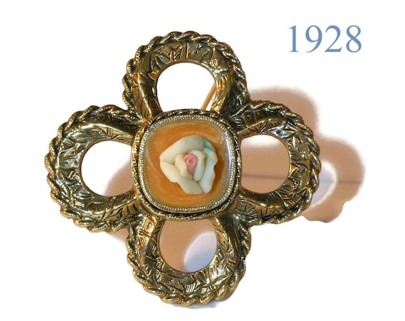 1928 porcelain rose bud, pink in white, on mustard gold enamel swirl cabochon inside gold clover rope like frame