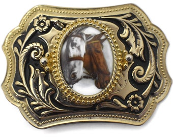 Horse belt buckle, a pair of horses, cameo behind glass with gold rope frame atop black and gold swirl floral design
