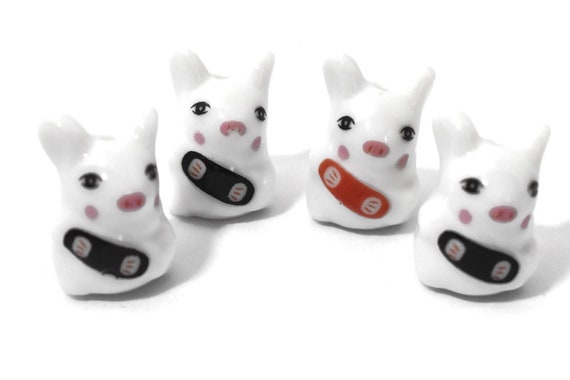 Porcelain pig beads, 4 piece lot, white piggy figurines, ceramic Kawaii, three matching with black banner, bandaid, accordian, one with red
