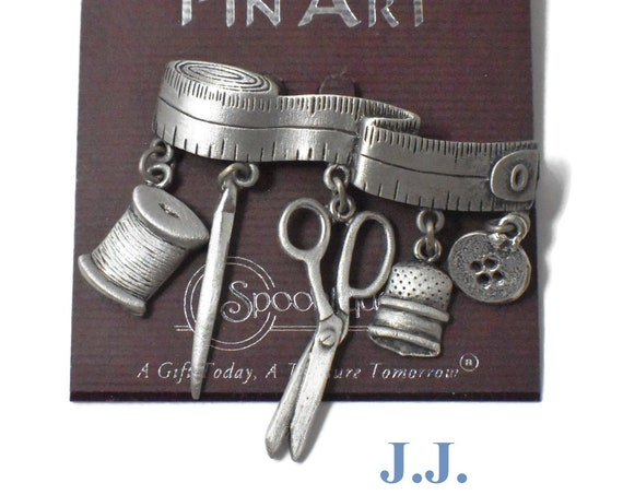 JJ pewter sewing brooch, tape measure with charms dangling, spool of thread, needle, scissors, thimble and button, nos Pin Art, Spoontiques