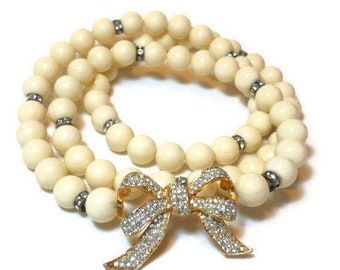 Sphinx faux pearl necklace, creamy faux pearls with rhinestone spacer accents and bow long necklace, cartouche missing, number mostly there