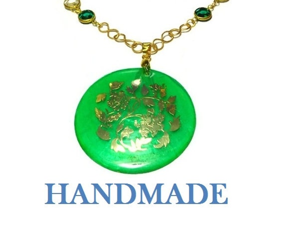 Handmade Capiz shell pendant with gold floral decal, wire wrapped infinity connectors, green and clear Swarovski crystal beads, gold plated