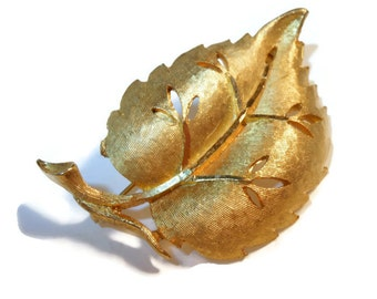 BSK figural leaf brooch with cut out work - gold plated brush work.