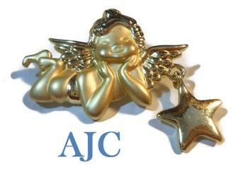 AJC cherub brooch, signed gold tone cherub brooch pin with star charm, matte and shiny finish